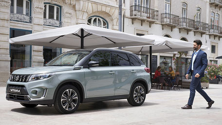 City scene of man walking to his Suzuki Vitara parked under a canopy in Ice Greyish Blue with Black Roof