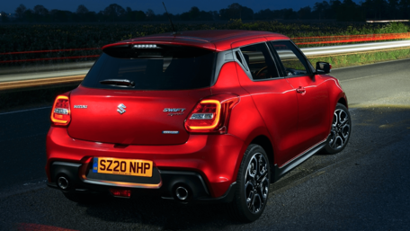 Rear view of Suzuki Swift Sport Hybrid in Burning Red Meallic driving at night on the open road
