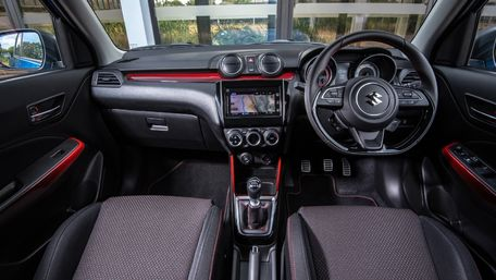 Interior of Suzuki Swift Sport Hybrid with bucketed sports seats - black interior with red trim