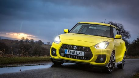 Front view of Suzuki Swift Sport Hybrid in Champion yellow headlights on driving on open road at dusk