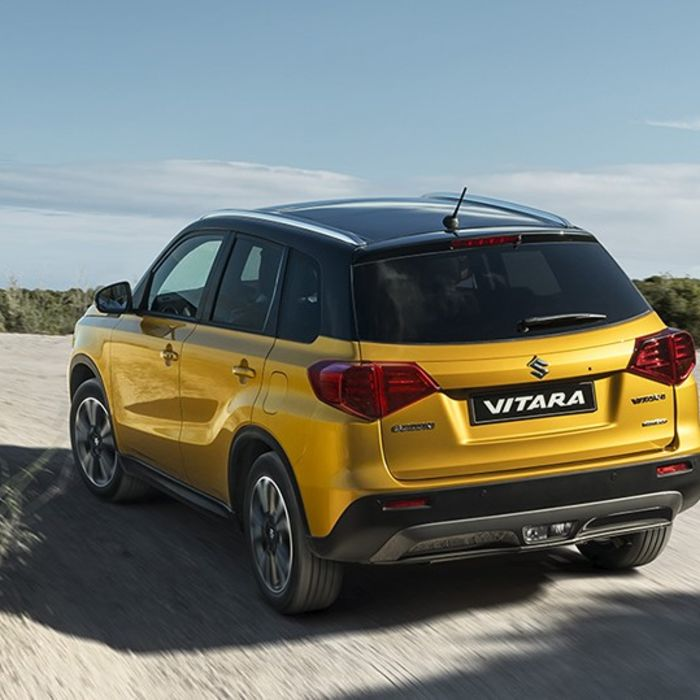 Side and rear three quarter view of Suzuki Vitara in Solar Yellow with Black roof