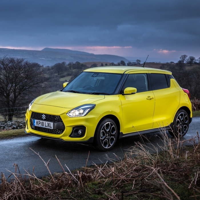 Front and side view of Suzuki Swift Sport Hybrid in Champion yellow driving in countryside