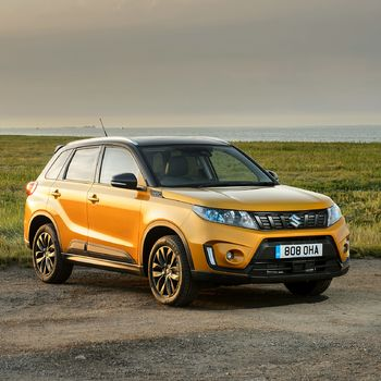 Front and side three quarter view of Suzuki Vitara SZ5 in Solar Yellow with Black Roof in countryside