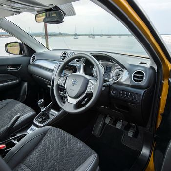 Interior View through open door of Suzuki Vitara in Solar Yellow showing fabric seats and steering wheel and dashboard