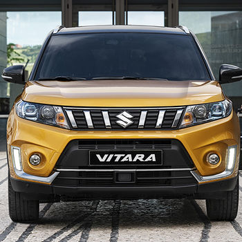 Front on view of Suzuki Vitara in Solar Yellow with Black Roof with man and woman walking towards it