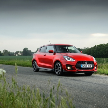 Side and front view of Suzuki Swift Sport Hybrid in Burning Red Metallic driving in the countryside