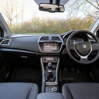 Black interior view of Suzuki SX4 S-Cross showing steering wheel and dashboard and gear console