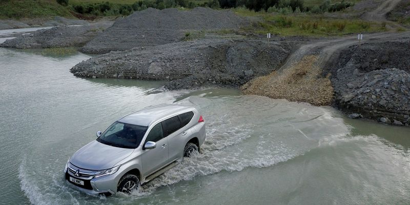 Mitsubishi Shogun Sport 4 in silver drives through a shallow river